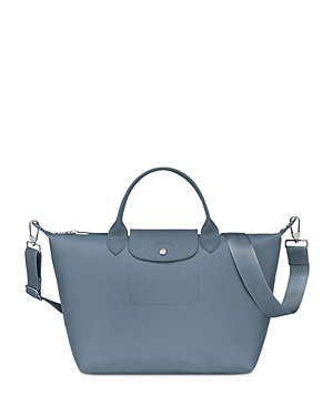 Longchamp debuts an all-new iteration of its much-loved Le Pliage tote: the Neo pairs textured leather trim with the French house\\\'s signature lightweight nylon in coordinating shades for a sleek, monochromatic look. With a spacious interior and handy shoulder strap, this carryall is primed for your daily commute.